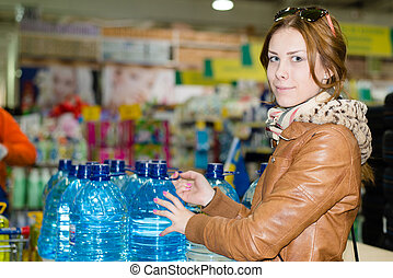 pretty woman buying a bottle of water looking at camera...