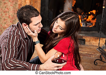 Pretty woman caress her man near fireplace