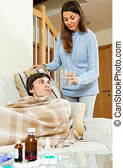 Pretty woman caring for sick man
