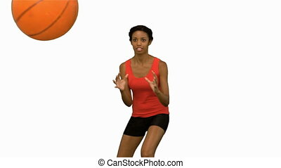 Pretty woman catching and throwing a basketball on white...
