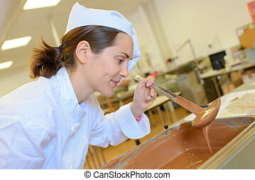 pretty woman checking fudge for pastries