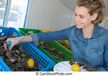 pretty woman choosing seafood in fish marketplace