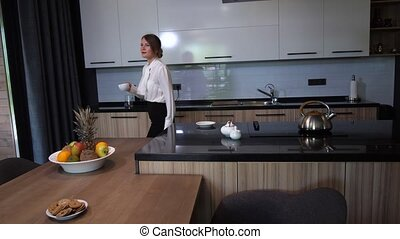 Pretty woman coming out from kitchen with coffee -...