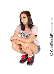 Pretty woman crouching on the floor in shorts