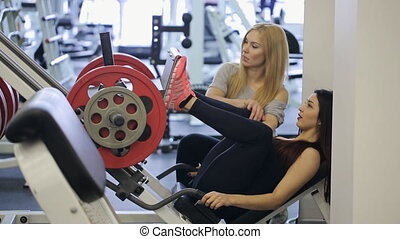 Pretty woman does exercises on simulator platform to train all muscles of legs