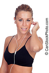 Pretty woman doing fitness istening music with headphones on whi