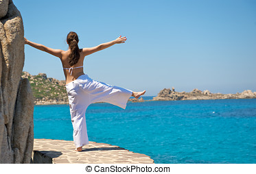 Pretty woman doing relaxation exercices with a sea view in...