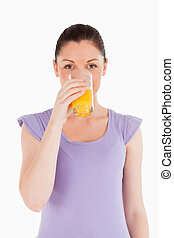 Pretty woman drinking a glass of orange juice while standing