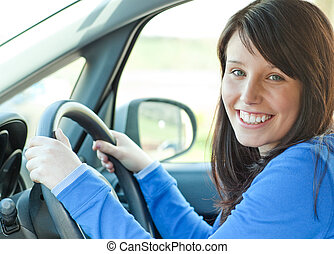 Pretty woman driving her car looking at the camera