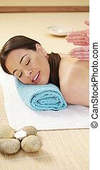 Pretty woman enjoying a lava stone massage