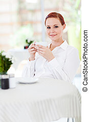 woman enjoying coffee in restaurant