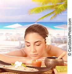 Pretty woman enjoying massage on the beach