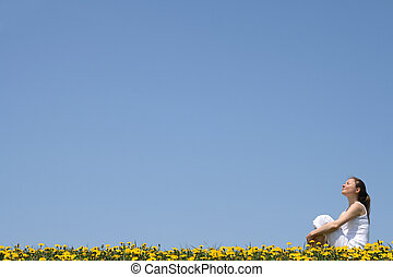 Pretty young woman enjoying sunshine and fresh air in a flowering field.