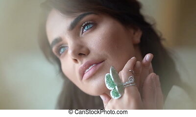 sexy woman of model appearance looks into the frame. chic emerald butterfly ring video