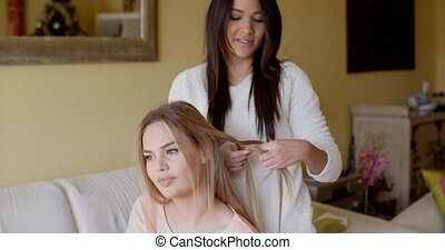 Kind Pretty Woman Fixing the Long Blond Hair of her Best Friend at Home.