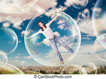 Pretty woman flying in the sky in big soap bubble