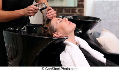 Pretty woman getting her hair washed at the hair salon