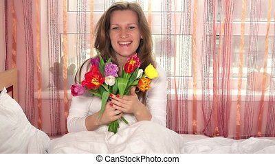 Pretty woman girl with colorful tulips and looking at camera and smelling flower