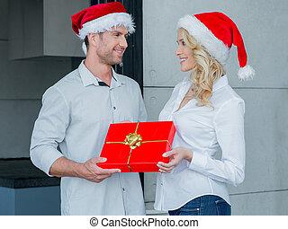 Pretty woman giving her husband a Christmas gift