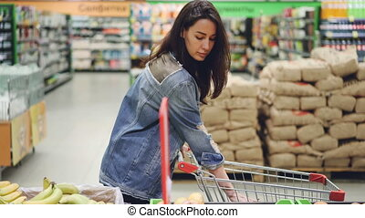Pretty woman happy customer is buying fruit in supermarket choosing bananas and apples and putting them in shopping cart. Healthy lifestyle and shops concept.