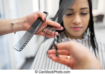 Pretty woman having hair cut in salon