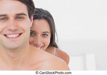 Pretty woman hiding behind shirtless man