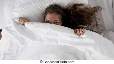 Pretty woman hiding under blanket - Top view happy cheerful...