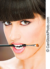 woman hold make up brush between teeth