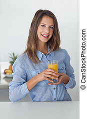 Pretty woman holding a glass of orange juice