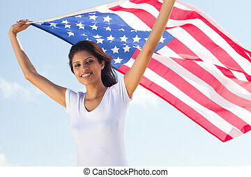 pretty woman holding american flag over her  head