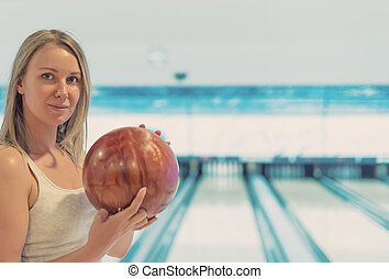 Pretty woman holding ball in bowling club.