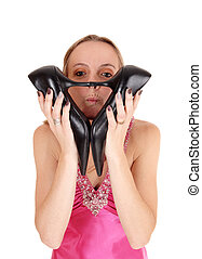 Pretty woman holding her heels over face