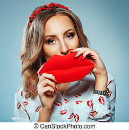 Pretty woman holding in hands big red lips, toy kiss-shaped