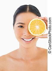 Pretty woman holding orange slice