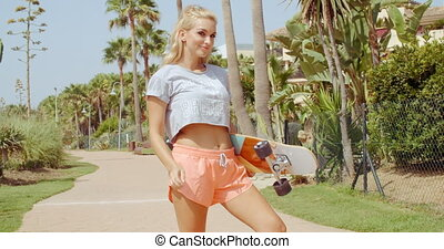 Pretty Woman Holding Skateboard at the Pathway