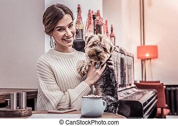 Pretty woman hugging her puppy visiting cafe