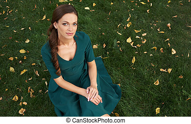 pretty woman in a dress sitting on green grass