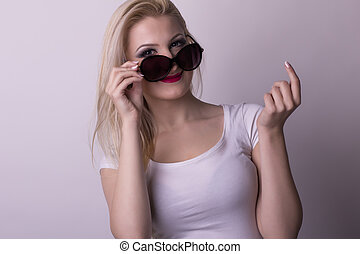 Pretty woman in a glasses on a grey background