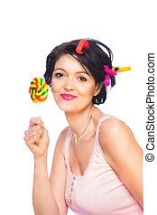 Pretty woman in a short shirt with a lollipop and colorful curlers
