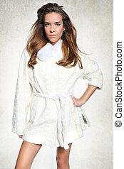 Pretty woman in a white fur coat