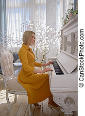 Woman in a yellow dress at the piano