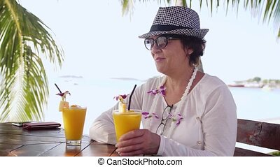 Pretty woman in aged wearing sunglasses and hat drinking fresh orange juice with straw on beach cafe during summer holidays.