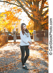Pretty woman in autumn style at sunset