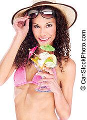 woman in bikini holding cup of fruits