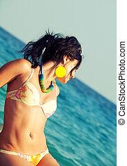 woman in bikini laying at sea rocks