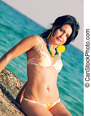pretty woman in bikini seating at sea rocks