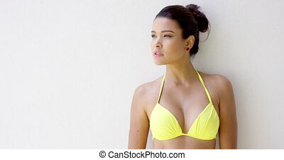 Pretty woman in bikini top beside blank wall