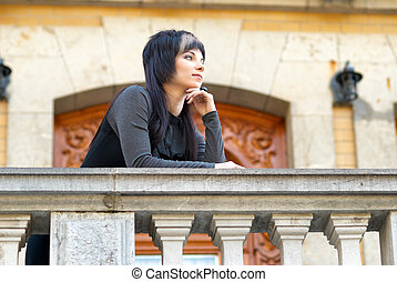 Pretty woman in black dress on the balcony