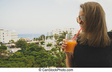 Pretty woman in black dress with glass of juice on vacation.