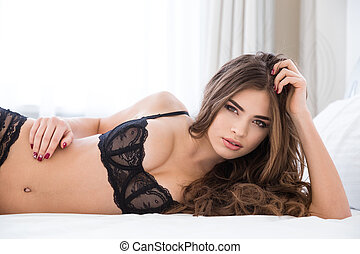 Pretty woman in black lingerie lying on the bed
